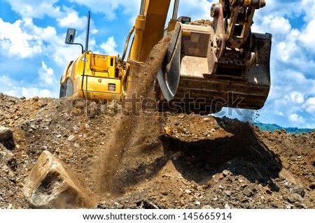 heavy duty construction excavator moving earth and sand on construction site, against a cloudy background - stock photo