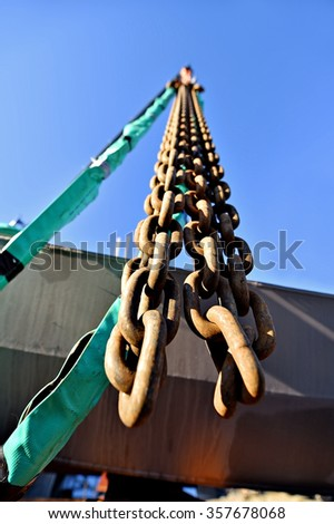 Heavy duty industrial chain hooked up on a construction crane - stock photo