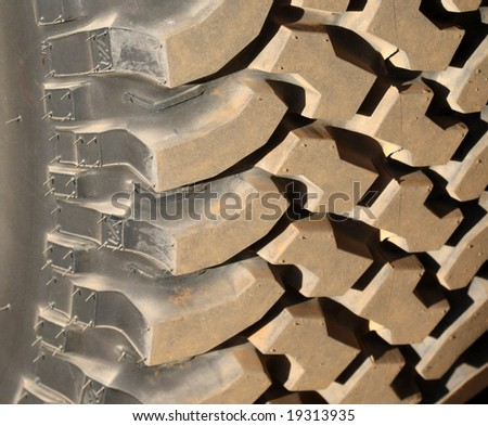 Heavy duty tread on an offroad tire provides interesting contrast and texture in this closeup picture. - stock photo