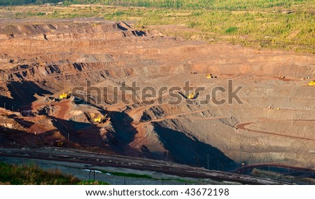 Heavy equipment digs and hauls ore inside an enormus open pit mine of Kursk Magnetic Anomaly - stock photo