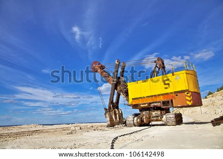 Heavy excavator in quarry for the extraction of gravel. Against the background of blue sky. - stock photo