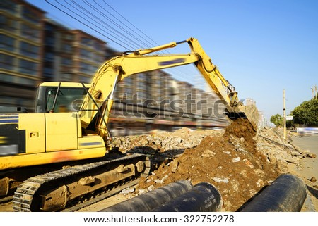 Heavy excavator unloading sand during road construction works  - stock photo