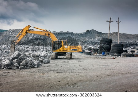 Heavy excavator with shovel standing on hill with rocks - stock photo