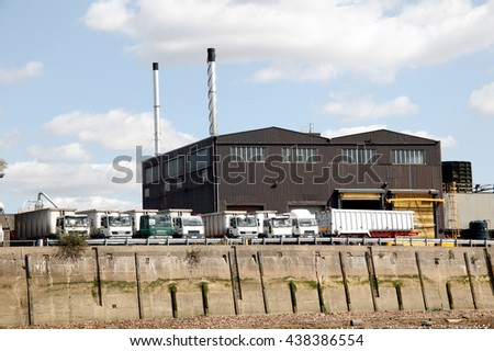 Heavy goods trucks parked at a factory loading bay