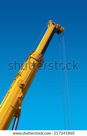 Heavy Hydraulic Crane on Blue Sky / Big and yellow construction hydraulic crane for heavy lifting on blue sky - stock photo