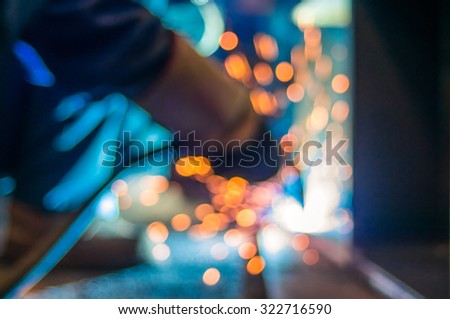 Heavy industry welder worker in protective mask hand holding arc welding torch working on metal construction - stock photo