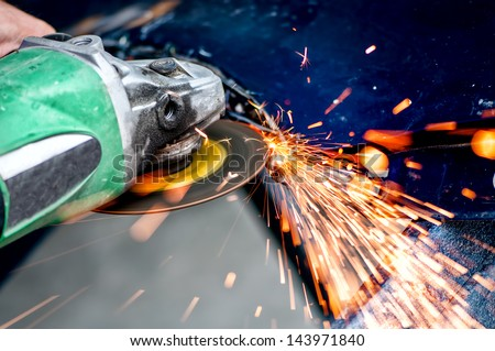 Heavy industry worker cutting steel with angle grinder in workshop, at car service - stock photo