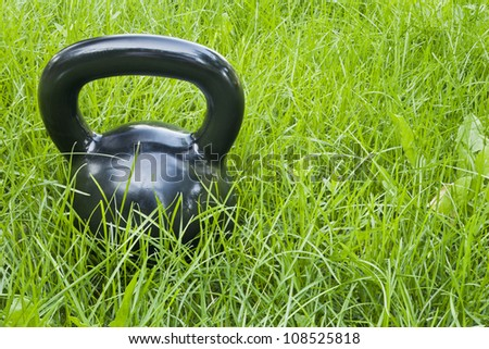 heavy iron  kettlebell in green grass - outdoor fitness concept - stock photo