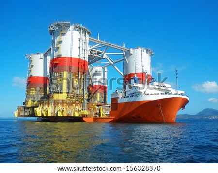 Heavy lift cargo ship transporting an oil rig - stock photo