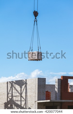 heavy load hanging on the hook of a crane on the construction of brick under construction  - stock photo