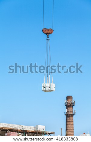 heavy load hanging on the hook of a crane under construction and the construction of a brick chimney boiler  - stock photo