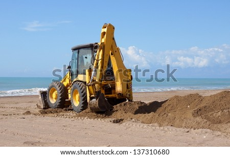 heavy machinery is used to move sand on a beach - stock photo
