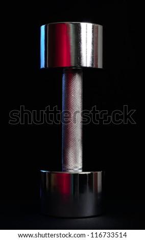 Heavy Metal Dumbbell on Black Background - stock photo