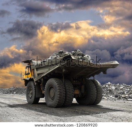 Heavy mining truck driving along the opencast - stock photo