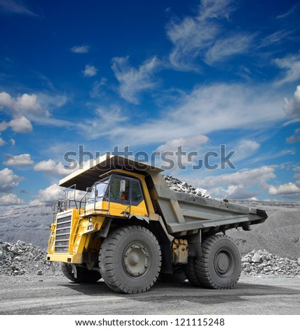 Heavy mining truck driving through the iron ore opencast - stock photo