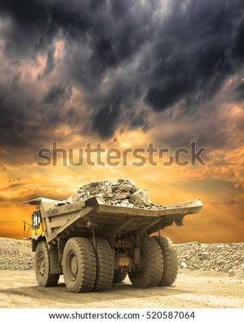 Heavy mining truck loaded with iron ore driving along the opencast on a stormy sunset