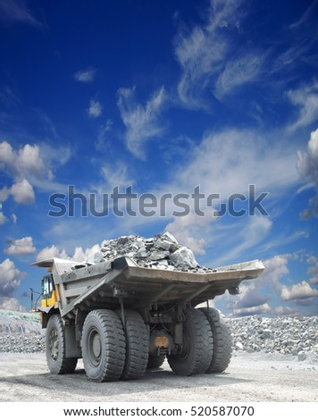 Heavy mining truck loaded with iron ore driving along the opencast on a sunny day