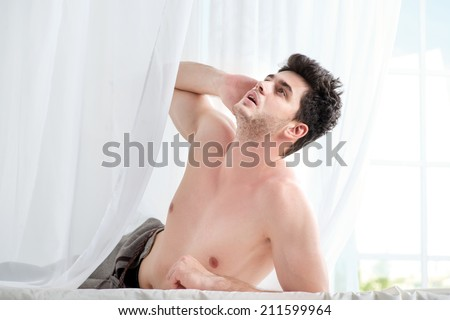 Heavy morning. Stripped handsome man lying in bed with a naked torso. Young boy lying in bed with his pants unbuttoned and his hand on the head