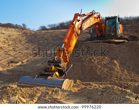 Heavy orange excavator at work in a sandpit seen from the front - stock photo