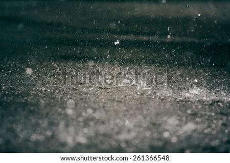 Heavy rain drops on asphalt. - stock photo