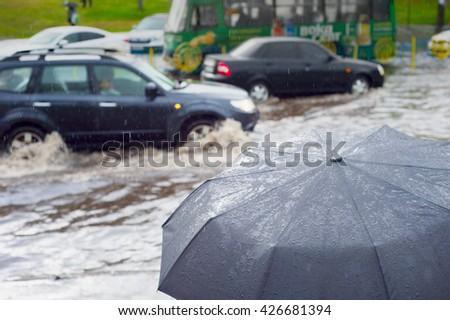 Heavy rain in the city. Sharpness on umbrella - stock photo