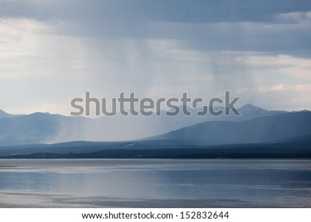 Heavy rain shower over Marsh Lake Yukon Territory Canada and distant mountain range - stock photo
