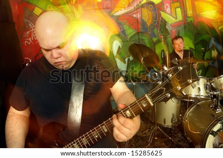 Heavy rock band playing. Shot with strobes and slow shutter speed to create lighting atmosphere and blur effects.  Slight movement visible on both players.