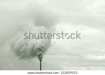 Heavy smoke billowing from an industrial chimney against a cloudy sky.