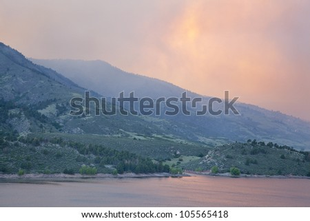 heavy smoke from High Park wildfire obscuring the sun and sky over Horsetooth Reservoir and foothills near Fort Collins, Colorado, June 10, 2012 - stock photo