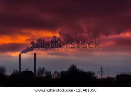 Heavy smoke spewed from coal powered plant smoke stacks under dramatic red sunset - stock photo