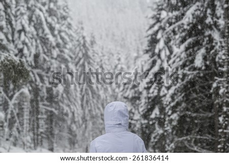 Heavy snow falls on a man with a winter jacket in the woods