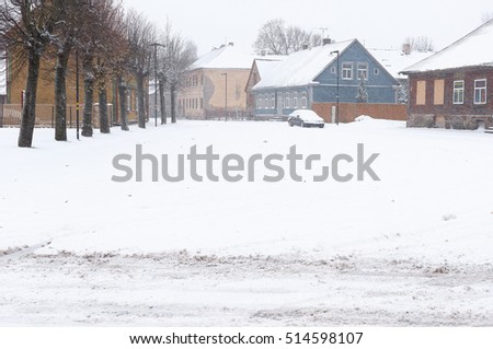 Heavy snowfall in the city streets, houses and machine snowy.