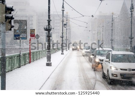 Heavy Traffic on One of  Prague's Bridges in Winter With Falling Snow on Misty Day - stock photo