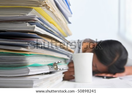 Heavy workload concept with pile of paper and woman on background. Selective focus - stock photo
