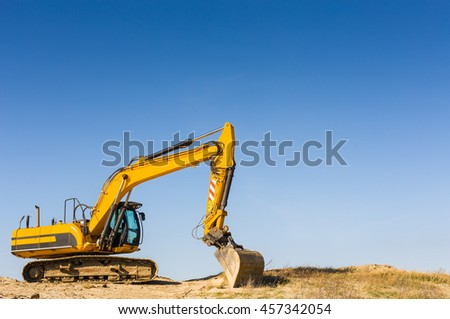 Heavy yellow excavator on the beach under a clear blue sky. Brand names removed. - stock photo