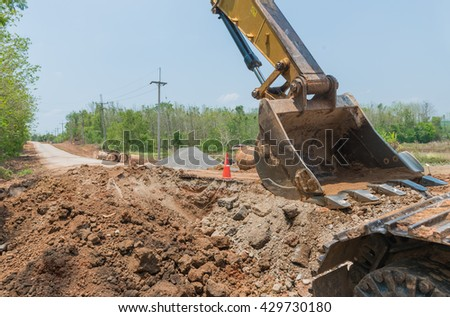 heavy yellow excavator with shovel standing during earthmoving works outdoors at construction site - stock photo