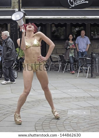 HEBDEN BRIDGE, UK - JUNE 2013: #Visitors perform a series of cheap yet glamorous incidents in the central square of Hebden Bridge to the enhance humdrum realities  of  everyday life, June 29th 2013.