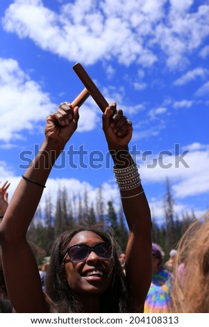 Heber City, Utah, USA 7/4/14. A woman with percussion sticks playing music at the rainbow gathering in the local forest.