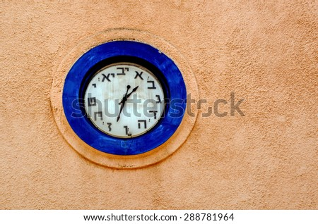 Hebrew clock on a wall of a synagogue in Israel. copyspace - stock photo