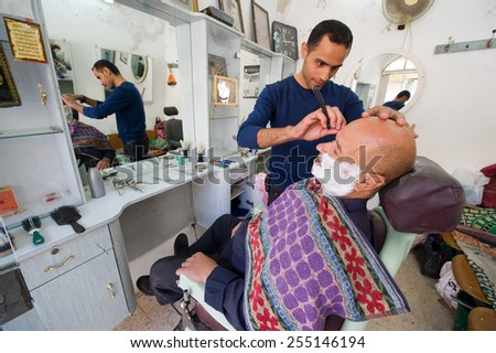 HEBRON, ISRAEL - 10 OCT, 2014: A barber is shaving a man in his small barbershop in the center of the old city of Hebron - stock photo