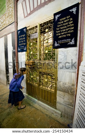 HEBRON, ISRAEL, 10 OCT, 2014: A young girl is watching through the bars of an iron door to the tomb of patriarch Abraham. The tombs of the patriarchs are situated in the Cave of Machpelah in Hebron - stock photo