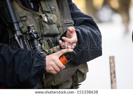 HEBRON, PALESTINIAN TERRITORY - FEBRUARY 22: An Israeli soldier prepares to pull the pin on a flash-bang during a protest against the Israeli occupation in Hebron, West Bank, February 22, 2013.  - stock photo