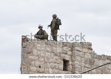 HEBRON, PALESTINIAN TERRITORY - FEBRUARY 22: Israeli soldiers occupy a rooftop during a protest against the Israeli occupation in the West Bank city of Hebron, February 22, 2013. - stock photo
