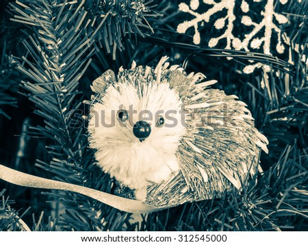 Hedgehog decoration in christmas tree, monochrome image - stock photo