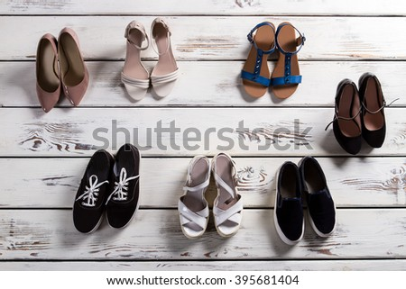 Heel shoes and casual keds. Stylish shoes on woodern floor. Lady's fashinable footwear. Shoes for warm season. - stock photo