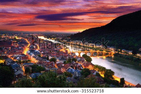 Heidelberg, Germany, aerial view at dusk, with dramatic sunset sky and the lights of the city, Neckar river and the Old Bridge - stock photo