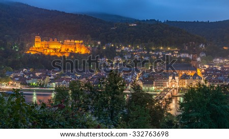 Heidelberg, Panorama Aerial View with Heidelberg Castle on the hill, Altstadt, The Church of the Jesuits, Holy Spirit, St. Peter's Church and the Old Bridge river Neckar illuminated at dusk, Germany