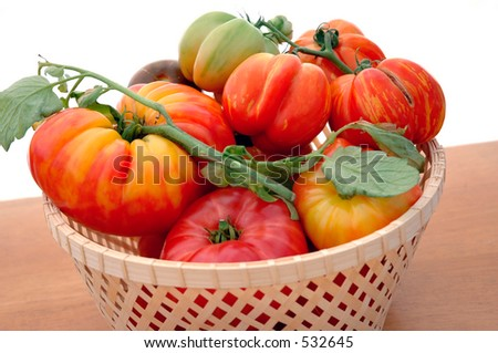 Heirloom tomatoes in basket on white background. - stock photo