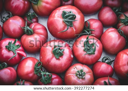 Heirloom tomatoes in display at a market. Organic, heirloom tomatoes, juicy and nutricious for sale at market - stock photo