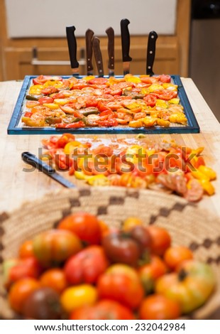 Heirloom tomatoes on a drying rack ready for a dehydrator - stock photo